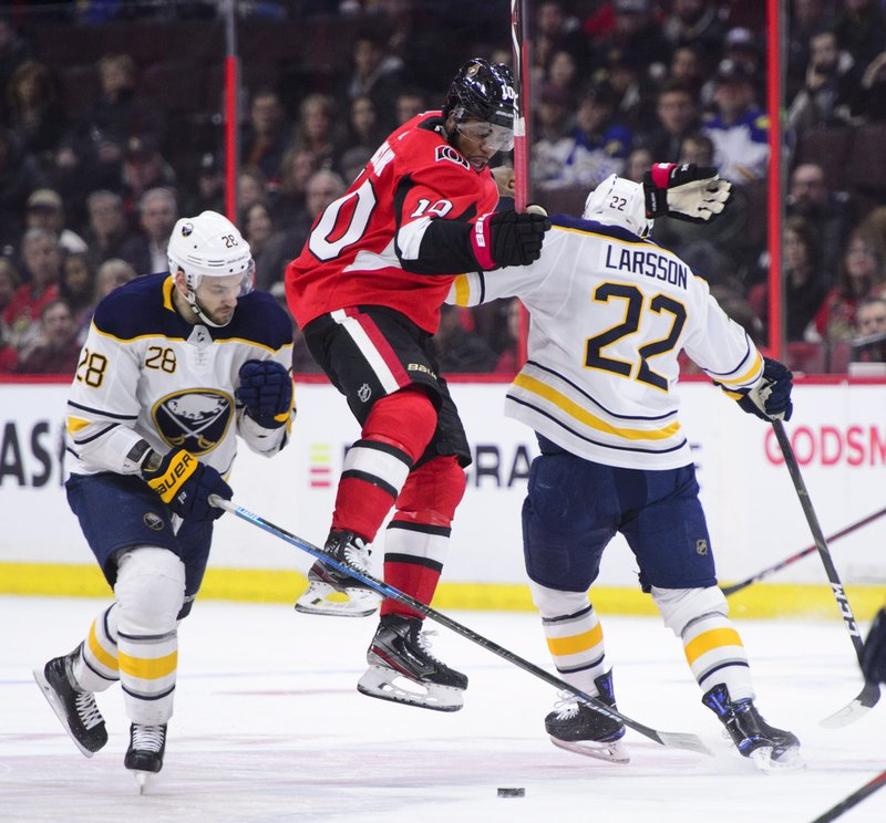 Ottawa Senators left wing Anthony Duclair (10) gets hit by Buffalo Sabres centre Johan Larsson (22) and Buffalo Sabres' Zemgus Girgensons (28) during first period NHL hockey action in Ottawa, Ontario, on Tuesday, March 26, 2019. (Sean Kilpatrick/The Canadian Press via AP)
