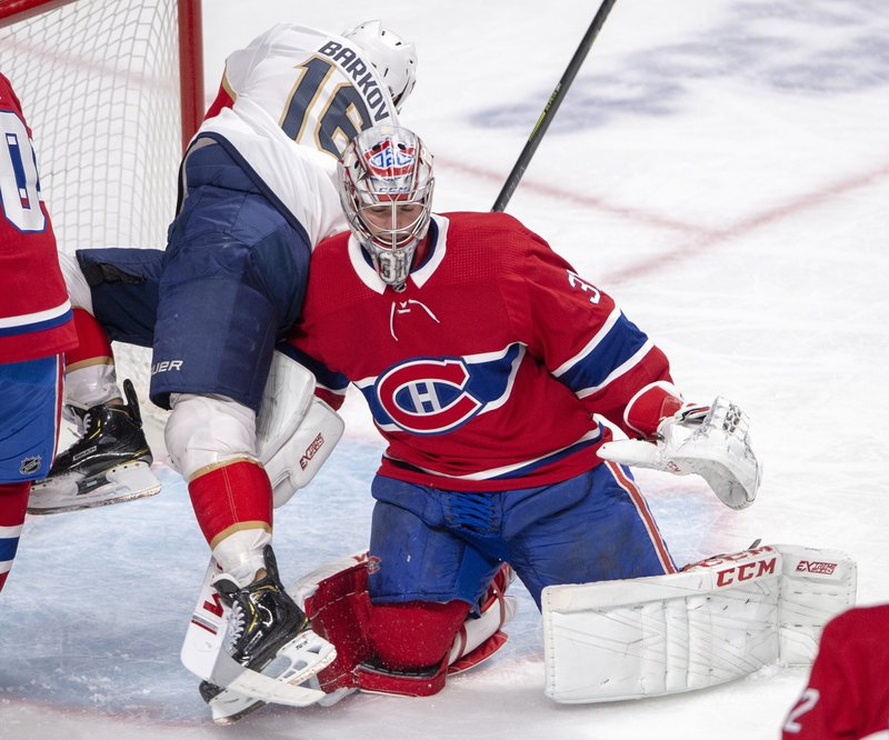 Florida Panthers center Aleksander Barkov (16) falls over Montreal Canadiens goaltender Carey Price (31) during the second period of an NHL hockey game Tuesday, March 26, 2019, in Montreal. (Ryan Remiorz/The Canadian Press via AP)