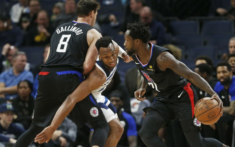 Minnesota Timberwolves' Josh Okogie, center, tries to get past Los Angeles Clippers' Danilo Gallinari, left, as Patrick Beverley in the first half of an NBA basketball game Tuesday, March 26, 2019, in Minneapolis. (AP Photo/Jim Mone)