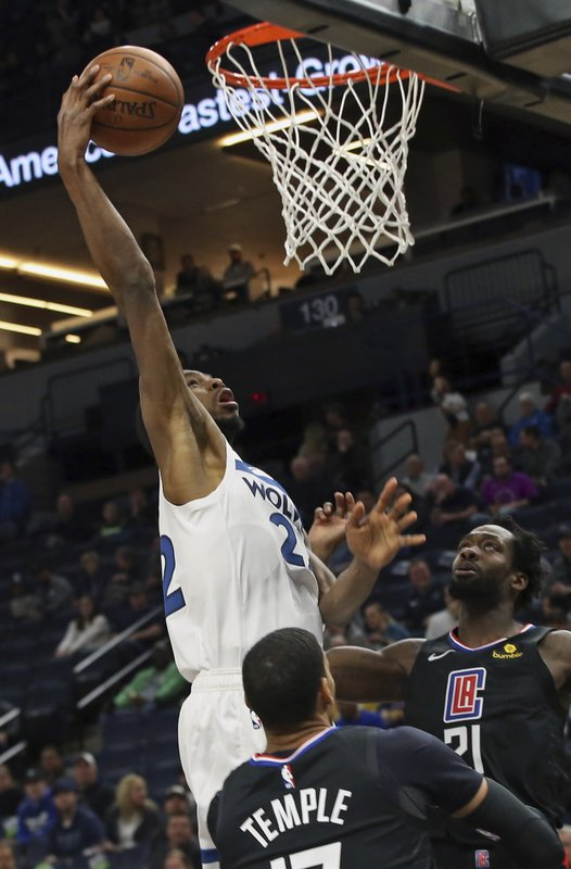 Minnesota Timberwolves' Andrew Wiggins, left, shoots as Los Angeles Clippers' Garrett Temple and Patrick Beverley, right, watch in the first half of an NBA basketball game Tuesday, March 26, 2019, in Minneapolis. (AP Photo/Jim Mone)