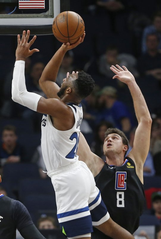 Minnesota Timberwolves' Josh Okogie, left, shoots as Los Angeles Clippers' Danilo Gallinari defends in the second half of an NBA basketball game Tuesday, March 26, 2019, in Minneapolis. (AP Photo/Jim Mone)