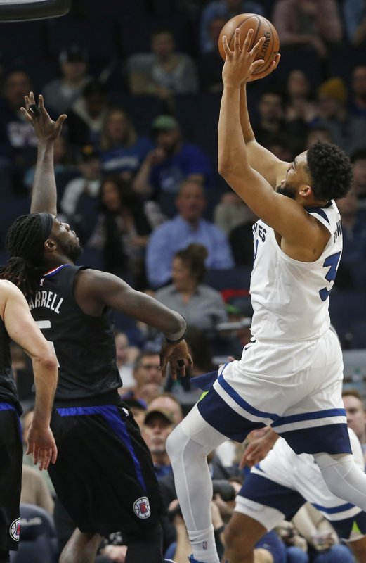 Minnesota Timberwolves' Karl-Anthony Towns, right, shoots over Los Angeles Clippers' Montrezl Harrell in the second half of an NBA basketball game Tuesday, March 26, 2019, in Minneapolis. (AP Photo/Jim Mone)