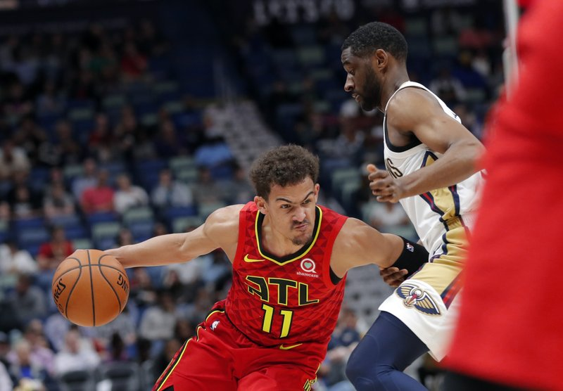 Atlanta Hawks guard Trae Young (11) drives to the basket against New Orleans Pelicans guard Ian Clark in the first half of an NBA basketball game in New Orleans, Tuesday, March 26, 2019. (AP Photo/Gerald Herbert)