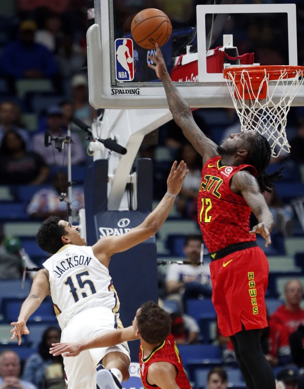 Atlanta Hawks forward Taurean Prince (12) tries to block a shot by New Orleans Pelicans guard Frank Jackson (15) in the first half of an NBA basketball game in New Orleans, Tuesday, March 26, 2019. (AP Photo/Gerald Herbert)