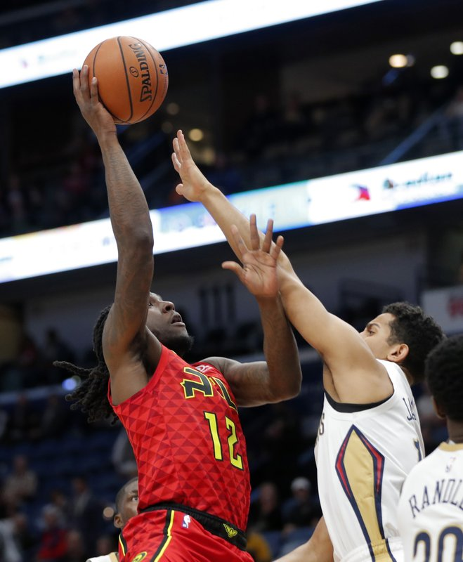 Atlanta Hawks forward Taurean Prince, left, goes to the basket against New Orleans Pelicans guard Frank Jackson, right, in the first half of an NBA basketball game in New Orleans, Tuesday, March 26, 2019. (AP Photo/Gerald Herbert)