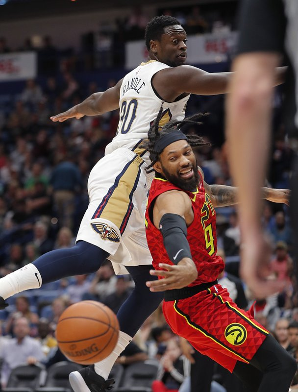 Atlanta Hawks forward DeAndre' Bembry, right, passes around New Orleans Pelicans center Julius Randle, left, in the first half of an NBA basketball game in New Orleans, Tuesday, March 26, 2019. (AP Photo/Gerald Herbert)