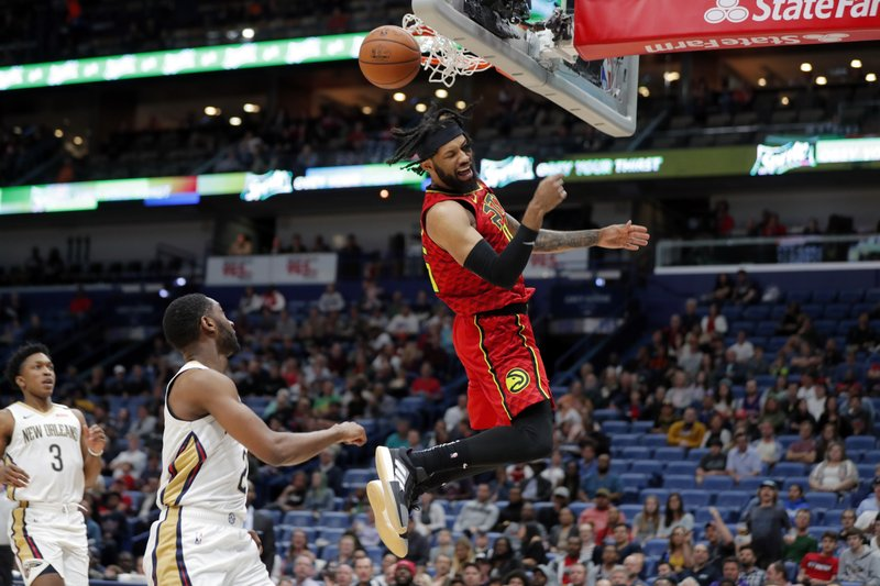 Atlanta Hawks forward DeAndre' Bembry slam dunks 0ver New Orleans Pelicans guard Ian Clark (2) in the first half of an NBA basketball game in New Orleans, Tuesday, March 26, 2019. (AP Photo/Gerald Herbert)