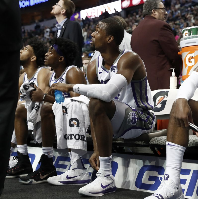 Sacramento Kings forward Harrison Barnes, center, looks up at the video board from the bench during a time out as the Dallas Mavericks play a video tribute to Barnes in the first half of an NBA basketball game in Dallas, Tuesday, March 26, 2019. (AP Photo/Tony Gutierrez)