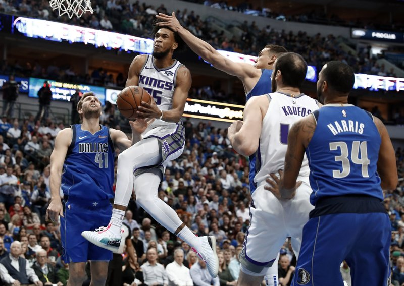 Sacramento Kings forward Marvin Bagley III (35) goes up for a shot over Dallas Mavericks' Dirk Nowitzki (41) as Kosta Koufos, second from right and Devin Harris (34) watch in the first half of an NBA basketball game in Dallas, Tuesday, March 26, 2019. (AP Photo/Tony Gutierrez)