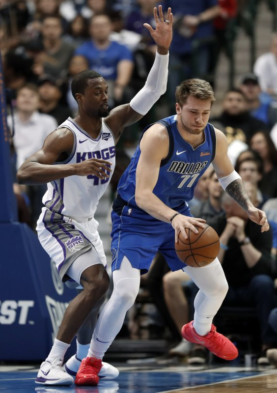 Sacramento Kings forward Harrison Barnes (40) defends as Dallas Mavericks forward Luka Doncic (77) works to the basket in the first half of an NBA basketball game in Dallas, Tuesday, March 26, 2019. (AP Photo/Tony Gutierrez)