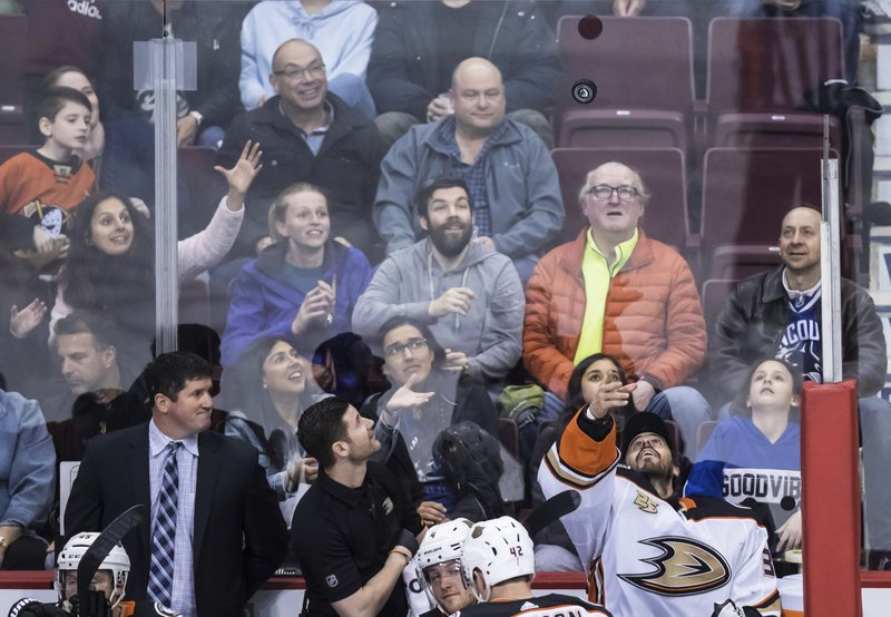Anaheim Ducks goalie Ryan Miller, front right, tosses a puck into the crowd after catching it when it went out of play during the second period of an NHL hockey game in Vancouver, British Columbia, Tuesday, March 26, 2019. (Darryl Dyck/The Canadian Press via AP)
