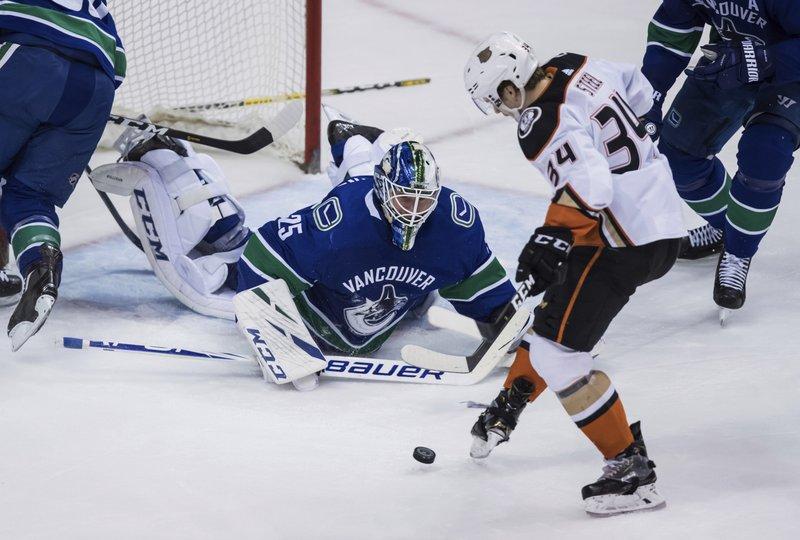 Anaheim Ducks' Sam Steel (34) kicks the puck ahead to his stick and scores against Vancouver Canucks goalie Jacob Markstrom (25), of Sweden, during the second period of an NHL hockey game in Vancouver, British Columbia, Tuesday, March 26, 2019. (Darryl Dyck/The Canadian Press via AP)