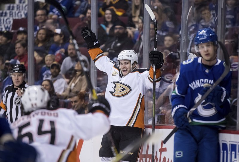 Anaheim Ducks' Sam Steel, back center, celebrates his goal as Vancouver Canucks' Elias Pettersson, right, of Sweden, looks on during the first period of an NHL hockey game in Vancouver, British Columbia, Tuesday, March 26, 2019. (Darryl Dyck/The Canadian Press via AP)