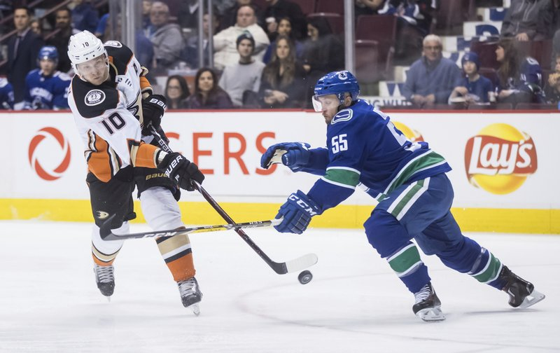 Anaheim Ducks' Corey Perry (10) takes a shot on goal as Vancouver Canucks' Alex Biega (55) defends during the first period of an NHL hockey game in Vancouver, British Columbia, Tuesday, March 26, 2019. (Darryl Dyck/The Canadian Press via AP)