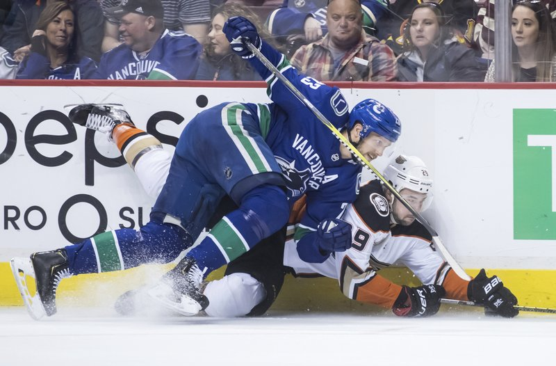 Vancouver Canucks' Alexander Edler, front, of Sweden, checks Anaheim Ducks' Devin Shore during the first period of an NHL hockey game in Vancouver, British Columbia, Tuesday, March 26, 2019. (Darryl Dyck/The Canadian Press via AP)