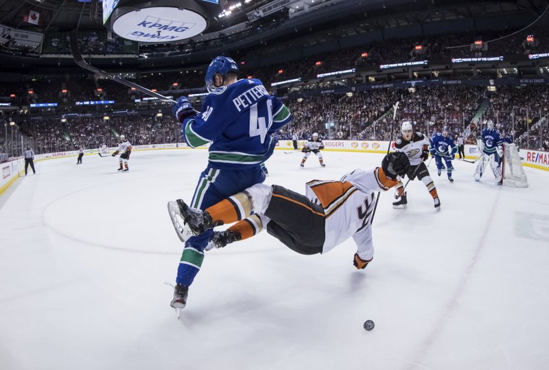 Vancouver Canucks' Elias Pettersson, left, of Sweden, and Anaheim Ducks' Sam Steel collide during the first period of an NHL hockey game in Vancouver, British Columbia, Tuesday, March 26, 2019. (Darryl Dyck/The Canadian Press via AP)