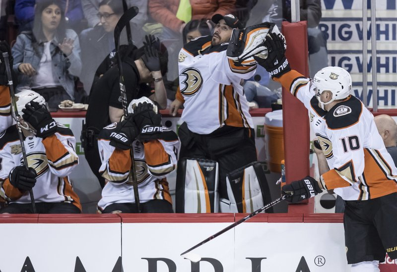 Anaheim Ducks goalie Ryan Miller, second right, catches a puck that went out of play as Corey Perry (10) reaches for it and Anaheim Ducks' Jaycob Megna, left, and Cam Fowler, second left, cover their faces during the second period of an NHL hockey game in Vancouver, British Columbia, Tuesday, March 26, 2019. (Darryl Dyck/The Canadian Press via AP)