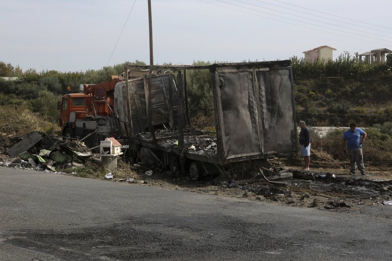 In this Saturday, Oct. 13, 2018 photo, a burnt-out truck is seen next to a highway at Sarakina, northern Greece, after a car transporting migrants and refugees crashed into a truck killing three people. (Ilias Kotsireas/InTime News via AP)