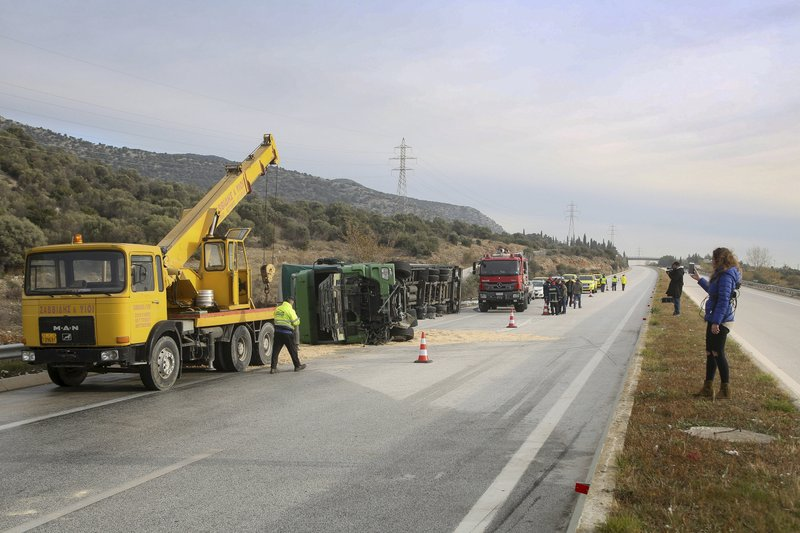 In this Thursday, Dec.13, 2018 photo, a crashed truck is seen on the highway near Keramoti village, northern Greece, after a car transporting migrants and refugees crashed into the truck killing three people. (Ilias Kotsireas/InTime News via AP)