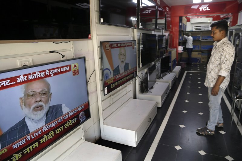 A salesman watches Indian prime minister Narendra Modi addressing the nation on a television  in Mumbai, India, Wednesday, March 27, 2019. (AP Photo/Rajanish Kakade)
