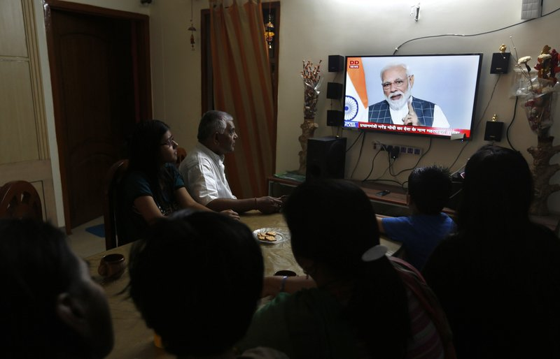 An Indian family watches Indian prime minister Narendra Modi addressing the nation on a television, in Prayagraj, Uttar Pradesh state, India, Wednesday, March 27, 2019. (AP Photo/Rajesh Kumar Singh)