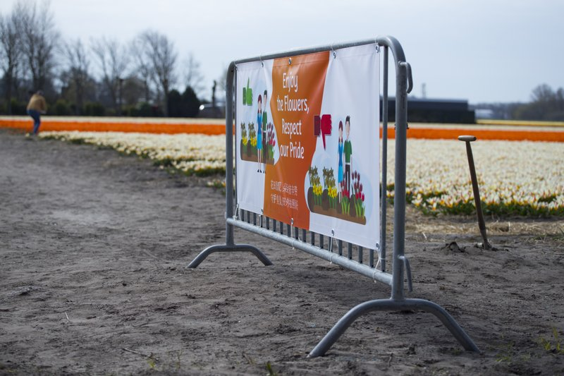A new sign asking tourists to stay out of the flower bulb fields is seen in Noordwijkerhout, near Lisse, Netherlands, Wednesday, March 27, 2019. (AP Photo/Peter Dejong)