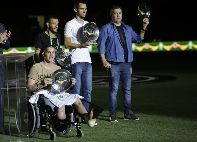FILE - In this Jan. 25, 2017 file photo, former Chapecoense players Neto, second from right, former goalkeeper Follmann, in wheelchair, Alan Ruschel, behind left, and radio soccer announcer Rafael Henzel, right, all plane crash survivors, are honored prior to a friendly soccer match between Brazil and Colombia at Nilton Santos stadium in Rio de Janeiro, Brazil. (AP Photo/Silvia Izquierdo, File)