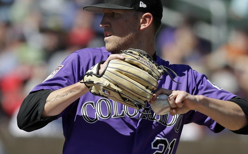 FILE - In this March 18, 2019, file photo, a tattoo of mountains extends down the right arm of left-handed Colorado Rockies starting pitcher Kyle Freeland as he throws against the Cincinnati Reds in a spring training baseball game  in Scottsdale, Ariz. (303), the elevation (5,280) and a silhouette of the Rocky Mountains. (AP Photo/Elaine Thompson, File)