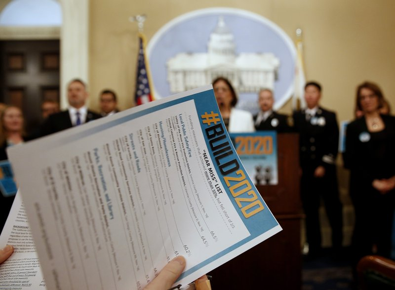 A reporter looks over a list of local government projects that failed to get the two-thirds votes needed for passage during a news conference held by Assemblywoman Cecilia Aguiar-Curry, D-Winters. (AP Photo/Rich Pedroncelli)