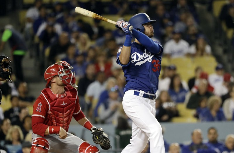 CORRECTS LOCATION TO LOS ANGELES - Los Angeles Dodgers' Cody Bellinger follows through on a three-run home run against the Los Angeles Angels during the second inning of a preseason baseball game Tuesday, March 26, 2019, in Los Angeles, Calif. (AP Photo/Marcio Jose Sanchez)