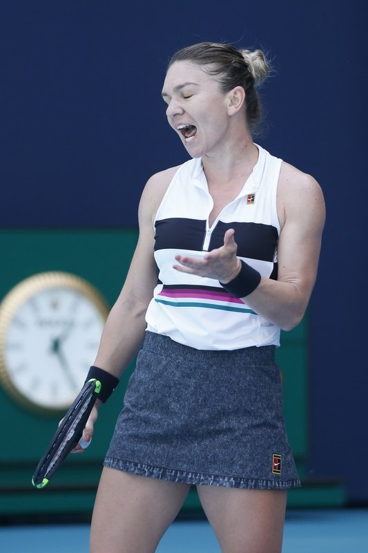 Simona Halep, of Romania, reacts after missing a shot by Qiang Wang, of China, during the Miami Open tennis tournament, Wednesday, March 27, 2019, in Miami Gardens, Fla. (AP Photo/Joel Auerbach)