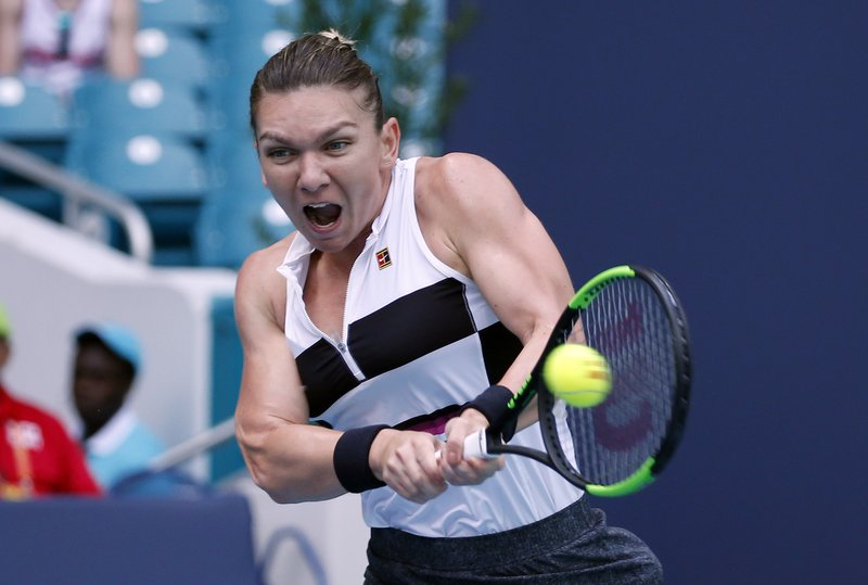 Simona Halep, of Romania, returns a volley to Qiang Wang, of China, during the Miami Open tennis tournament, Wednesday, March 27, 2019, in Miami Gardens, Fla. (AP Photo/Joel Auerbach)