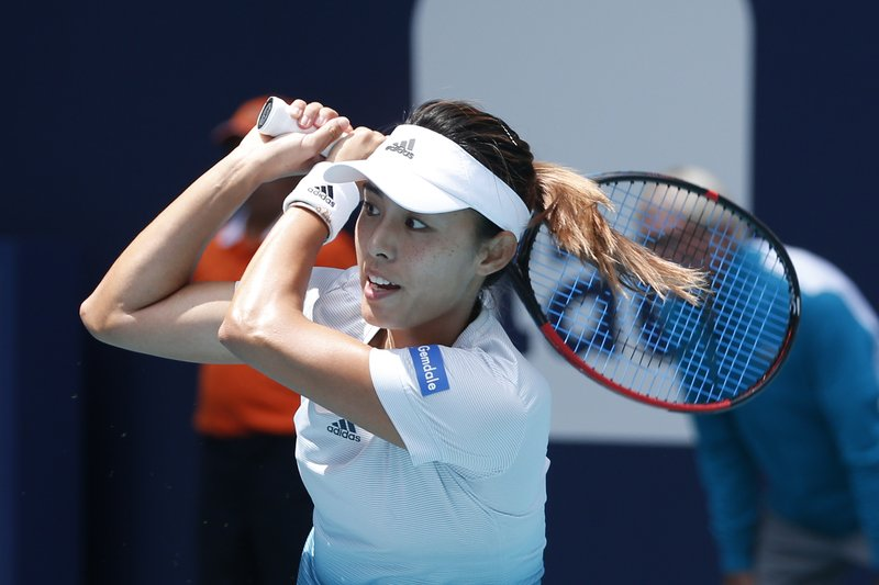 Qiang Wang, of China, returns a volley to Simona Halep, of Romania, during the Miami Open tennis tournament, Wednesday, March 27, 2019, in Miami Gardens, Fla. (AP Photo/Joel Auerbach)