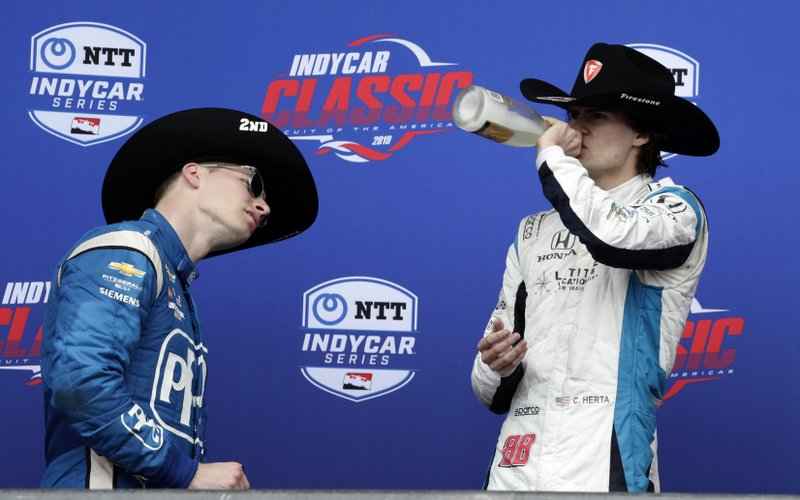 Colton Herta, right, takes a celebratory swig after winning the IndyCar Classic auto race, as second-place finisher Josef Newgarden, left, takes a closer look a the bottle label Sunday, March 24, 2019, in Austin, Texas. (AP Photo/Eric Gay)
