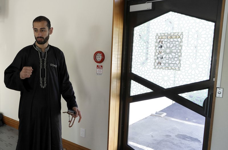In this March 27, 2019, photo, Al Noor mosque volunteer Khaled Alnobani gestures as explains his escape through a glass door panel when a gunman burst into the mosque on March 15 in Christchurch, New Zealand. (AP Photo/Mark Baker)