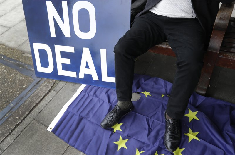 A pro Brexit campaigner sits with a banner outside Parliament in London, Wednesday, March 27, 2019. British lawmakers WERE preparing to vote Wednesday on alternatives for leaving the European Union as they seek to end an impasse following the overwhelming defeat of the deal negotiated by Prime Minister Theresa May. (AP Photo/Kirsty Wigglesworth)