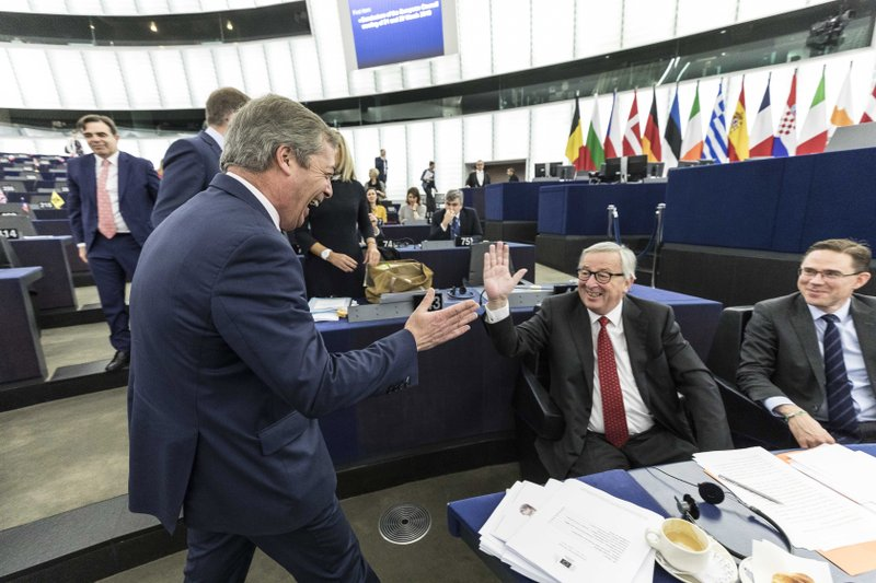 European Commission President Jean-Claude Juncker, center, greets Former U.K. Independence Party (UKIP) leader and member of the European Parliament Nigel Farage at the European Parliament in Strasbourg, France, Wednesday, March 27, 2019. (AP Photo/Jean-Francois Badias)
