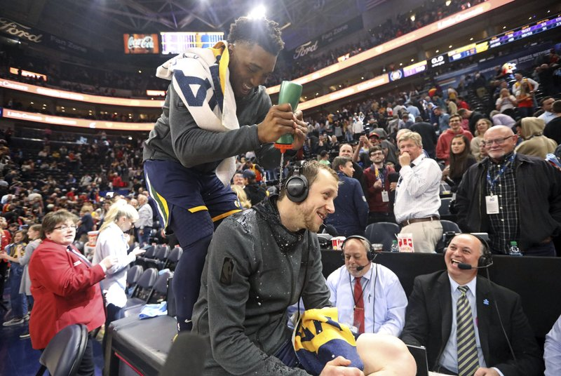 Utah Jazz guard Donovan Mitchell squirts liquid onto Joe Ingles, seated, following the team's NBA basketball game against the Los Angeles Lakers on Wednesday, March 27, 2019, in Salt Lake City. (AP Photo/Rick Bowmer)