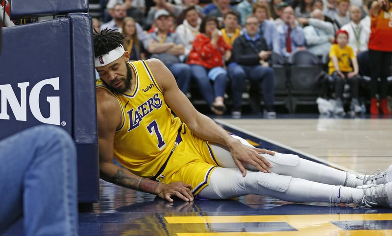 Los Angeles Lakers center JaVale McGee (7) lies against the stanchion after falling to the court during the second half of the team's NBA basketball game against the Utah Jazz on Wednesday, March 27, 2019, in Salt Lake City. (AP Photo/Rick Bowmer)
