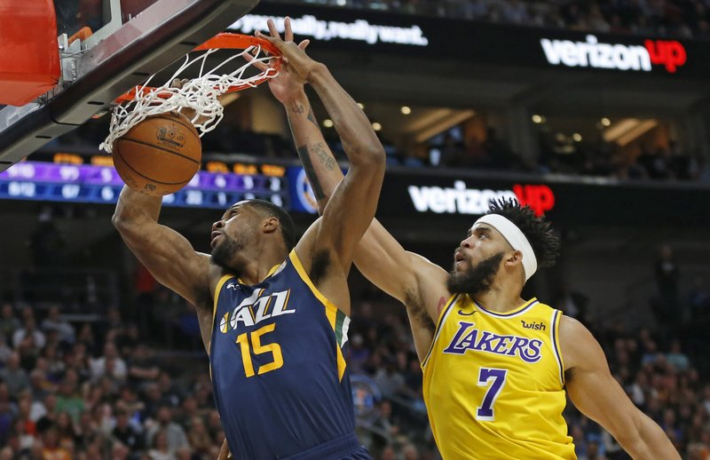 Utah Jazz forward Derrick Favors (15) dunks next to Los Angeles Lakers center JaVale McGee (7) during the second half of an NBA basketball game Wednesday, March 27, 2019, in Salt Lake City. (AP Photo/Rick Bowmer)