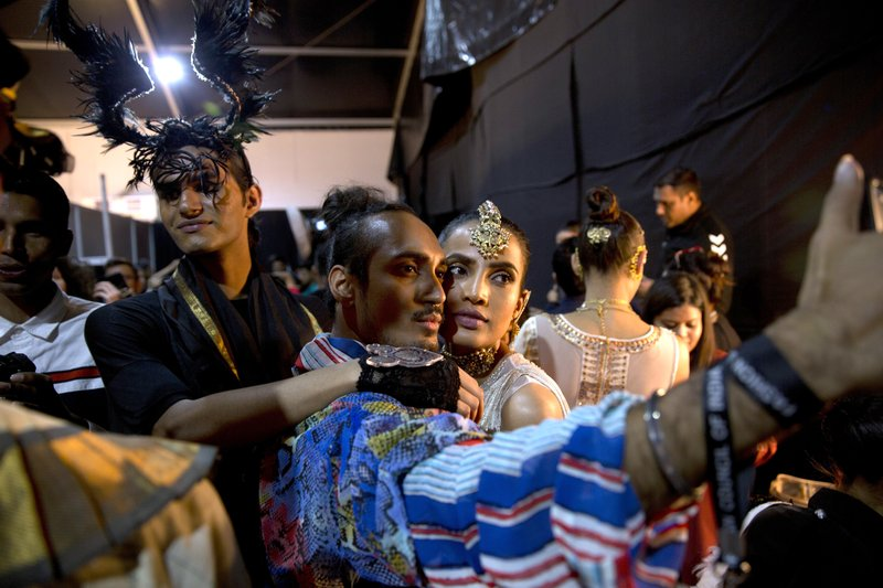 In this Saturday, March 16, 2019, photo, a designer takes a selfie with a model before the start of a catwalk during the Lotus Makeup India Fashion Week, in New Delhi, India. (AP Photo/Manish Swarup)