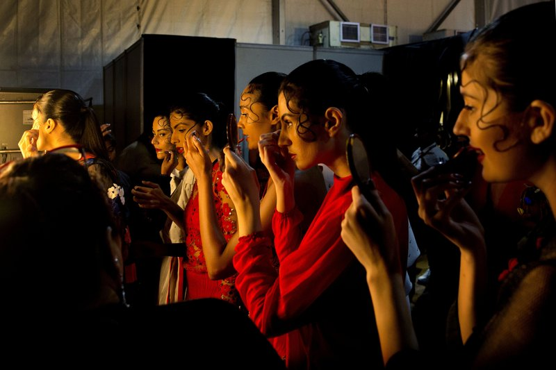 In this Wednesday, March 13, 2019, photo, models touch up their makeup before a show during the Lotus Makeup India Fashion Week, in New Delhi, India. (AP Photo/Manish Swarup)