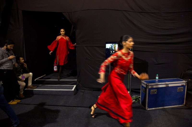 In this Wednesday, March 13, 2019, photo, models rush for a quick change of outfit in between a ramp walk during the Lotus Makeup India Fashion Week, in New Delhi, India. (AP Photo/Manish Swarup)