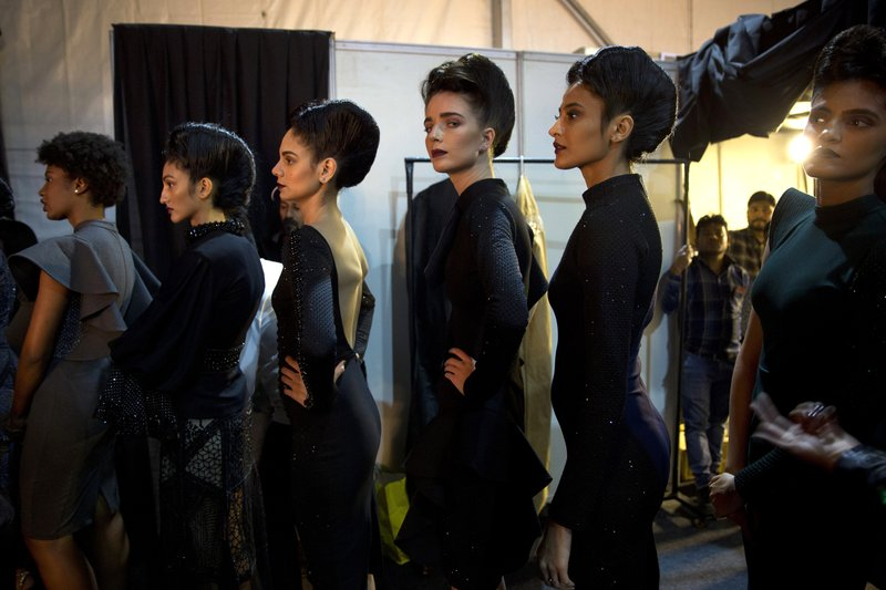 In this Saturday, March 16, 2019, photo, models line up backstage before the start of a catwalk during Lotus Makeup India Fashion Week, in New Delhi, India. (AP Photo/Manish Swarup)