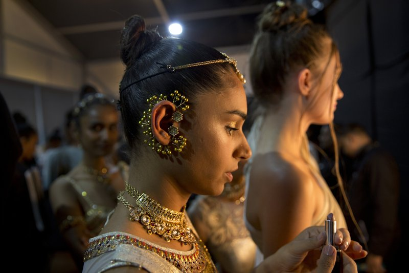In this Saturday, March 16, 2019, photo, models touches up her makeup before walking the ramp during Lotus Makeup India Fashion Week, in New Delhi, India. (AP Photo/Manish Swarup)