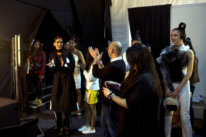 In this Thursday, March 14, 2019, photo, models, back stage managers and designers applaud at the end of a show during the Lotus Makeup India Fashion Week, in New Delhi, India. (AP Photo/Manish Swarup)