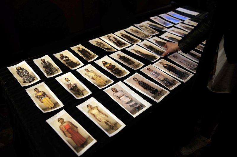 In this Monday, March 11, 2019, photo, a model looks at the line up and outfits planned during a fitting session ahead of the Lotus Makeup India Fashion Week, in New Delhi, India. (AP Photo/Manish Swarup)