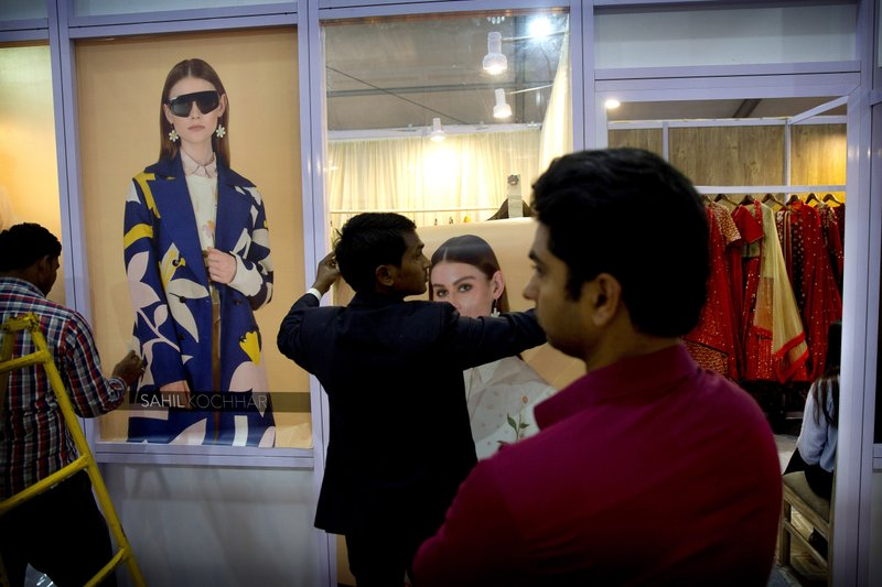 In this Wednesday, March 13, 2019, photo, workers put up posters of models outside a fashion designer's stall in an exhibition during Lotus Makeup India Fashion Week, in New Delhi, India. (AP Photo/Manish Swarup)