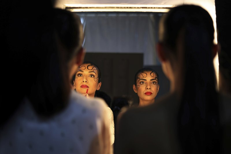 In this Wednesday, March 13, 2019, photo, models work on finishing touches before walking the ramp during Lotus Makeup India Fashion Week, in New Delhi, India. (AP Photo/Manish Swarup)