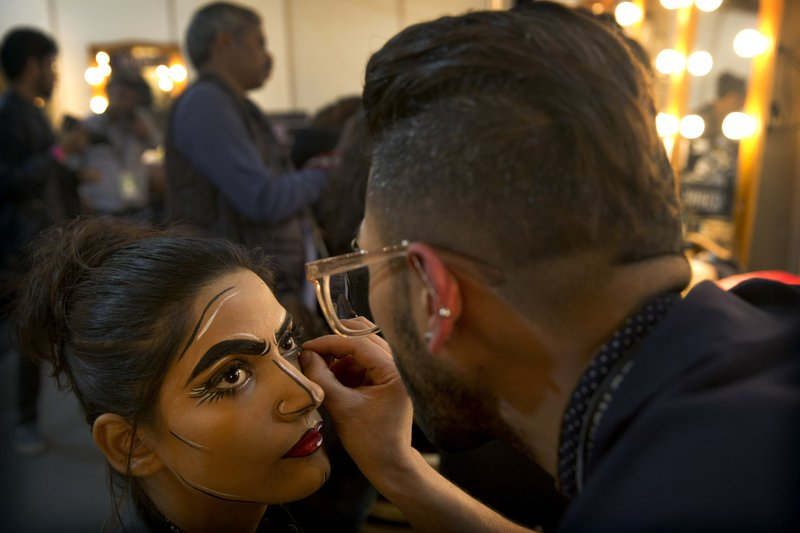 In this Thursday, March 14, 2019, photo, a makeup artist applies eyeliner to a model before a show during Lotus Makeup India Fashion Week, in New Delhi, India. (AP Photo/Manish Swarup)